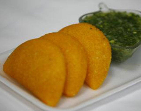 Fried empanadas with a cilantro-based dipping sauce